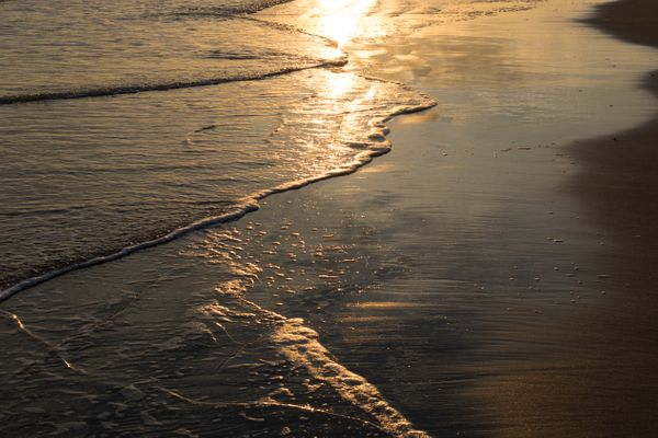 Waterlines during Ebb and Flow at the Beach during Sunset
